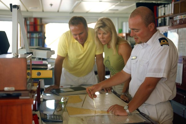 Couple with ship's navigator looking at nautical map