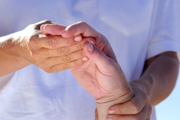 Physical therapist massaging hand of patient