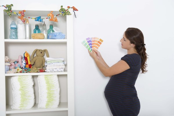 Pregnant woman with paint swatches in nursery