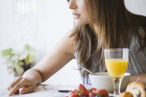 Woman reading map at breakfast table