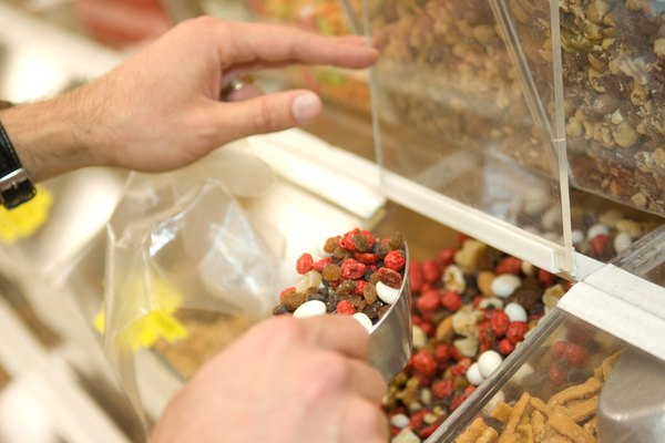 Man in health foods store with scoop of trail mix