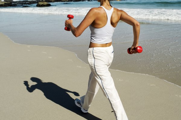 Rear view of a woman walking on the beach with dumbbells