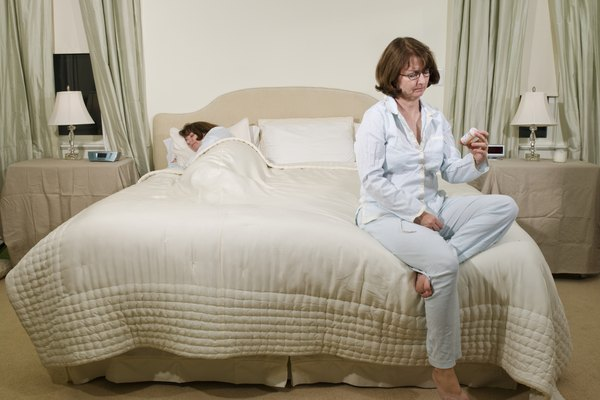 Mature woman sitting on bed looking at bottle of pills, other woman sleeping