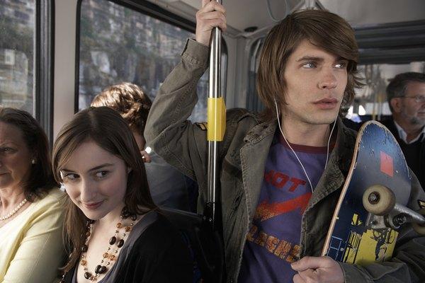 Personas viajando de pie en autobús.