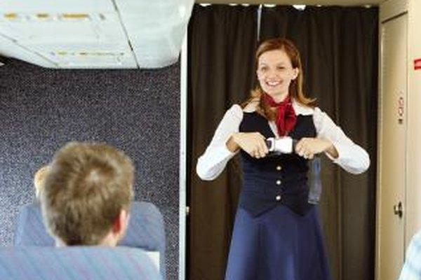 Los auxiliares a bordo demuestran las funciones de seguridad del avión antes de que el avión despegue.
