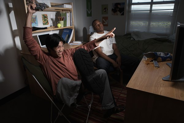 Two young men playing video game in dorm room, one cheering