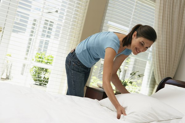 Woman making bed, smiling
