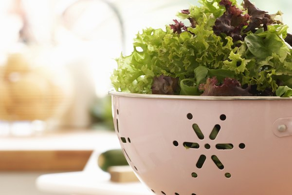 Mixed salad in colander on kitchen counter