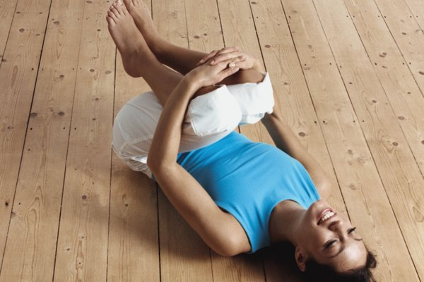 Smiling woman in little boat yoga position
