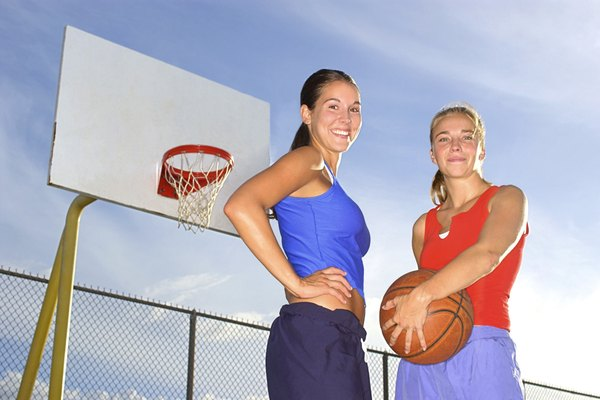 Low angle portrait of two women standing on a basketball court and smiling at the viewer