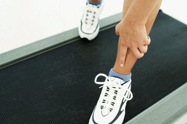 Woman touching her leg while standing on treadmill