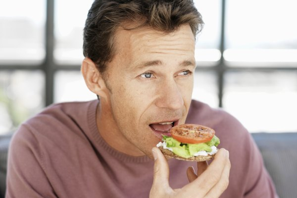 Mature man eating sandwich indoors, upper half