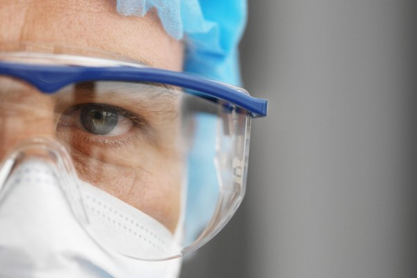 Close-up of a surgeon wearing scrubs and surgical mask and protective eyeglasses