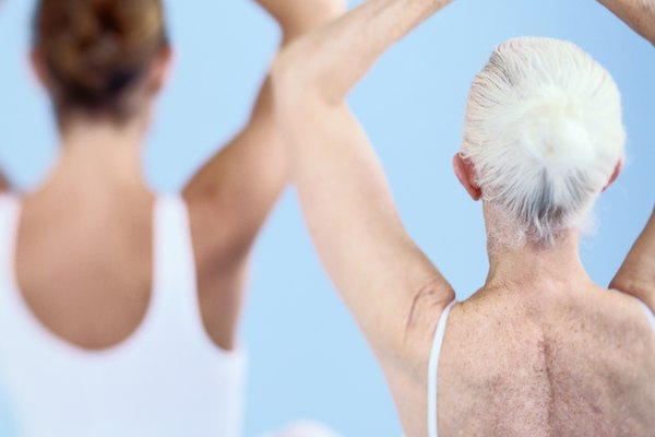 Young woman and elderly woman practicing yoga, rear view