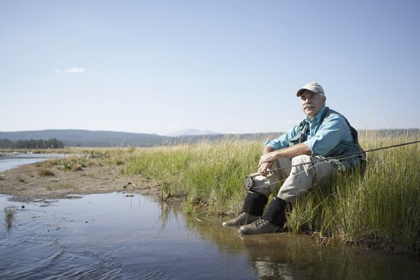 Portrait of senior man sitting on riverbank with fishing rod