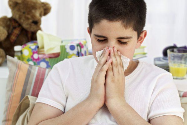 boy (12-14) sitting in bed and sneezing into a handkerchief