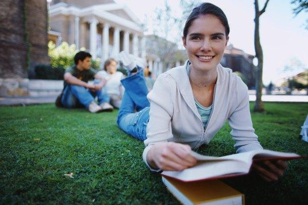 Un estudiante universitario que estudia en el césped.