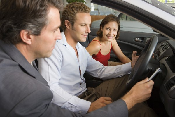 Car dealer assisting couple shopping for new car
