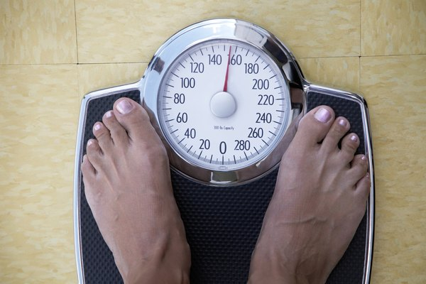 Low section view of a woman standing on a weighing scale