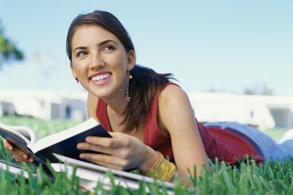 Close-up of a teenage girl lying on front on the grass, reading
