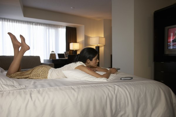 Businesswoman on hotel bed channel surfing