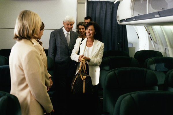 Female flight attendant standing in airplane welcoming passengers