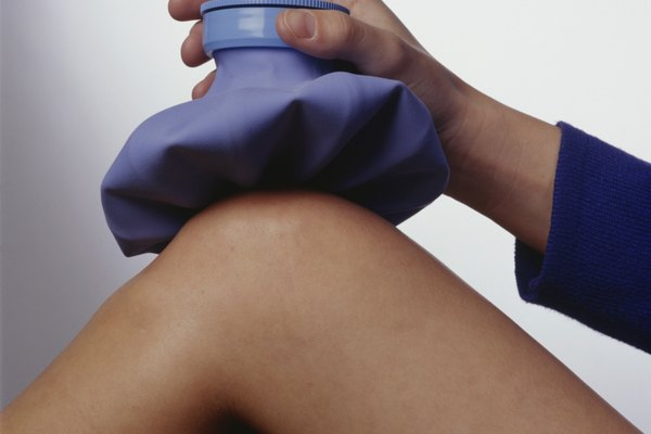 Woman applying ice pack to knee, (Close-up)