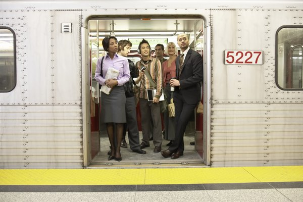 Medium group of people standing in subway train doorway