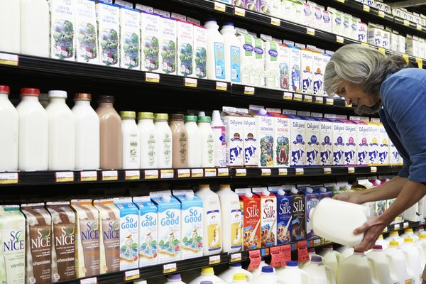 Mature woman reading milk label in supermarket, side view, close-up
