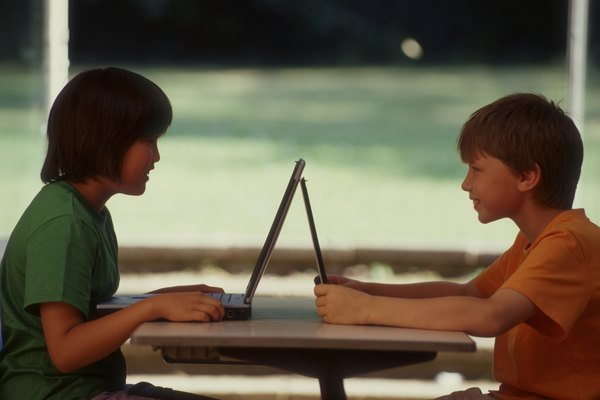 Two boys are playing on their computers.
