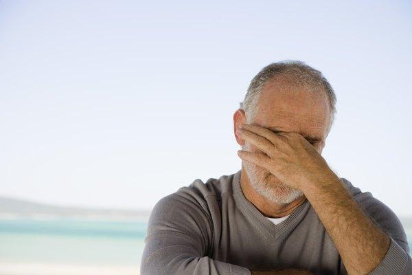 Stressed man rubbing eyes