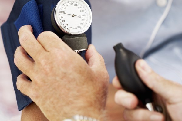 Close-up of a pair of human hands checking the blood pressure of a patient