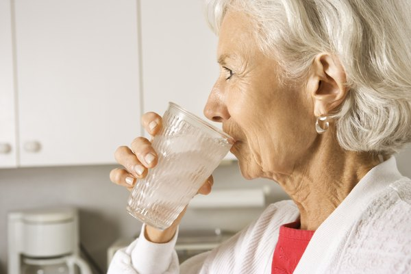 Elderly woman drinking glass of water