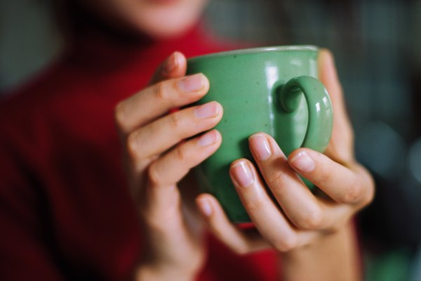 Close-up view of a person's hands holding a coffee mug
