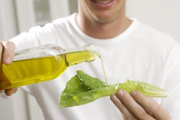 Man pouring olive oil on lettuce leaf