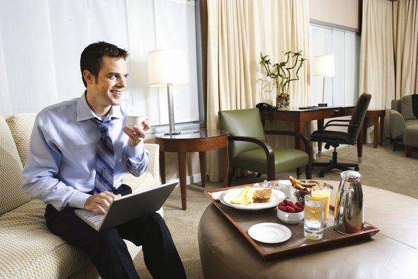 Businessman using computer and having breakfast