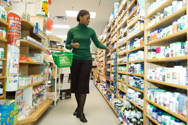 Woman shopping in aisle at health foods store