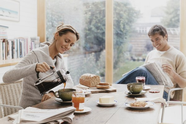 Couple Sits at a Table Over Breakfast, Woman Pouring Coffee in a Cup