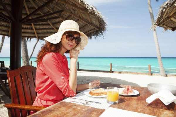 Fashion woman having breakfast on the beach