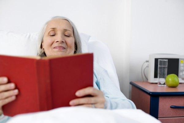 Mujer mayor leyendo un libro en la cama.
