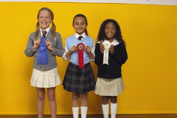 Tres niñas pequeñas con cintas de una feria de ciencias.