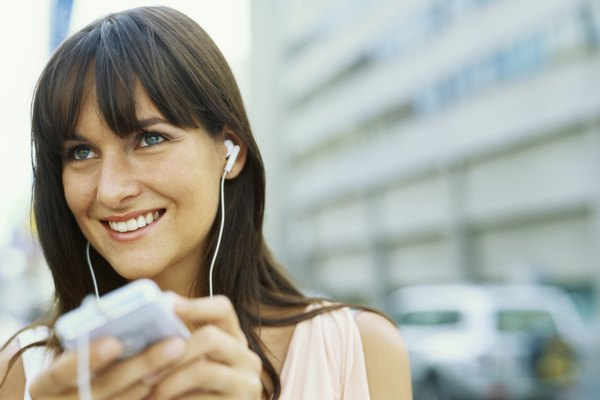 Close-up of a young woman listening to an MP3 player