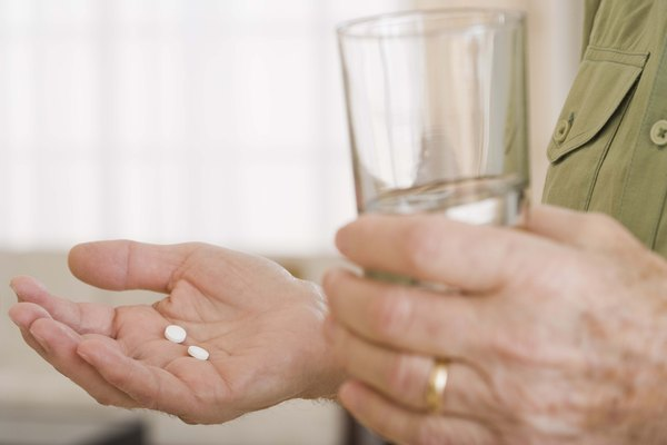 Person holding glass of water with pills