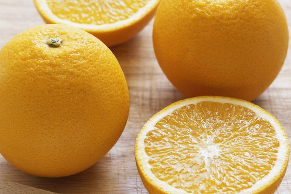 Whole and half oranges on wooden board by knife, close-up