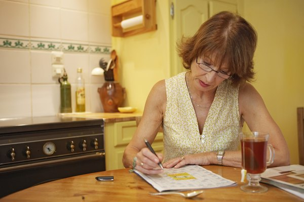 Mature woman wearing spectacles writing at kitchen table