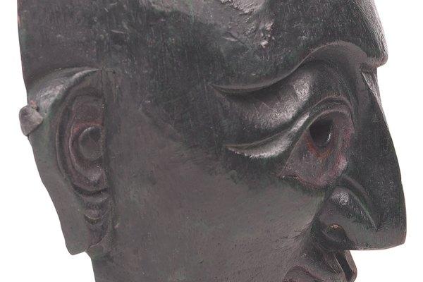 Presiona plumas, telas o hilo alrededor del borde exterior de la máscara antes de que se seque o pégalas en la máscara seca para decoración.