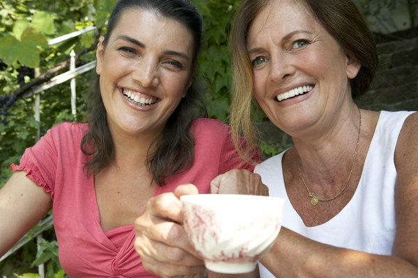 mature woman and daughter in garden drinking tea