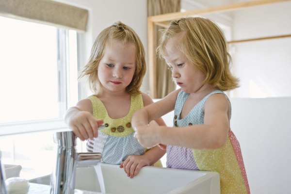 Twin girls at bathroom sink