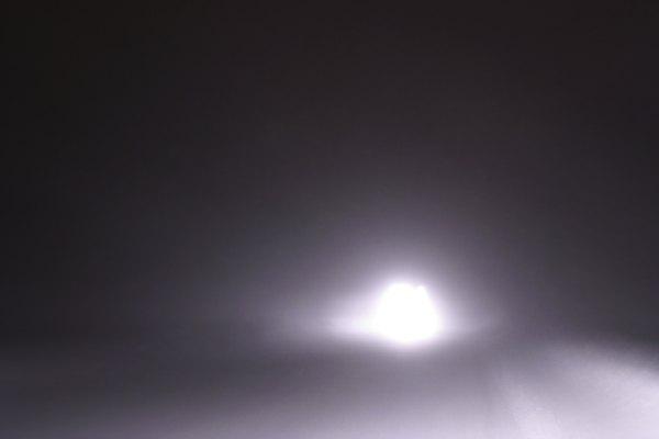 Luces frontales de un auto en la oscuridad.