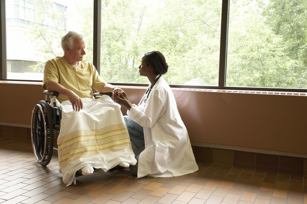 Doctor comforting patient in wheelchair by windows in hospital